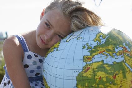 Mädchen hält Weltkugel im Arm